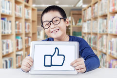 Boy showing thumb up symbol in library. Male elementary school student sitting in the library while holding a digital tablet to show thumb up icon Royalty Free Stock Images