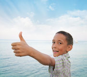 Boy showing thumbs-up against sea Stock Images