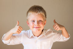 Boy showing thumbs up. Beautiful, happy, excited and confident boy showing thumbs up over grey background Royalty Free Stock Photo
