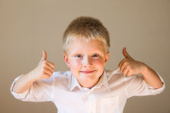 Boy showing thumbs up. Beautiful, happy, excited and confident boy showing thumbs up over grey background Stock Photography