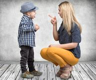 A young mother scolds her naughty little son.Boy showing tongue and teases my mom. stock image