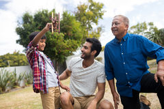 Boy showing toy airplane to father crouching by senior man Royalty Free Stock Images