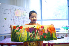 Boy showing tulip paiting in proud Royalty Free Stock Image