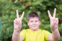 Boy showing victory sign gesture Stock Image