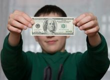A boy shows 100 dollars. A boy holds 100 dollars stock images