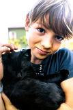 Boy shows  with affection his  black cat Royalty Free Stock Photo