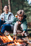 Boy shows beautiful roasred marshmallow on campfire Royalty Free Stock Images