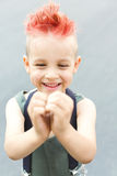 A boy shows his heart with his hands. A little boy with red hair. Child in uniform. The child indulges, croaks. Stock Images