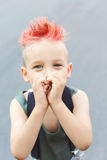 A boy shows his heart with his hands. A little boy with red hair. Child in uniform. The child indulges, croaks. Stock Photography
