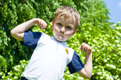 The boy shows his muscles. In an outdoor Royalty Free Stock Photos