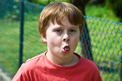 Boy shows his tongue Stock Photography