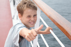 boy shows ok on deck of ship Stock Photo