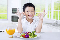 Boy shows OK sign with healthy food Stock Photography