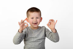 Boy shows okey sign. Little toothless boy with wide happy smile on face shows okey sign on gray background Stock Photography