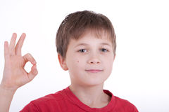 The boy shows a sign OK. Smiles Royalty Free Stock Photography