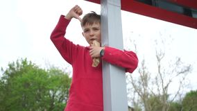 Boy shows thumb down gesture. The boy shows a gesture thumbs down, stands at the pillar stock video