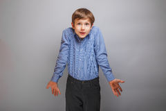 Boy shrugs from ignorance surprised. Boy shrugs from a ignorance surprised gray texture Stock Photography
