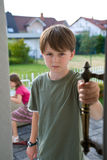 Boy Sibling Rivalry Conflict Door. A boy in a green t-shirt stands in an open door with an angry, troubled expression on his face, while his sister appears royalty free stock images