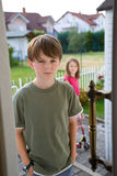 Boy Sibling Rivalry Conflict Door. A boy in a green t-shirt stands in an open door with an angry, troubled expression on his face, while his sister appears stock photo