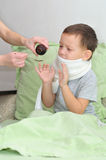 The boy is sick. Mom pours syrup. The boy refuses to drink Royalty Free Stock Photo