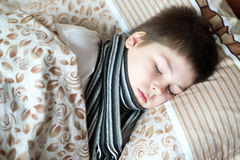 Boy with sick throat asleep in bed Royalty Free Stock Images