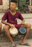 Boy on sidewalk playing bongos Havana Stock Images