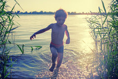 Boy silhouette running out of pond on the beach at Royalty Free Stock Photos