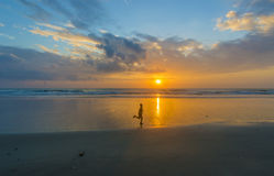 Boy silhouette and sunrise. Sunrise with children running foreground Royalty Free Stock Photos