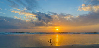 Boy silhouette and sunrise. Sunrise with children running foreground Royalty Free Stock Image