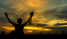 Boy silhoutte. Boy hold camera silhoutte with orange skies Stock Photo