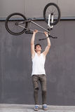 Boy with silver bike overhead at grey wall background Stock Photography
