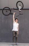 Boy with silver bike overhead at grey wall background Royalty Free Stock Photography