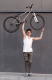 Boy with silver bike overhead at grey wall background Stock Photos