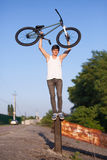 The boy with silver bike overhead standing on an iron pole Stock Photography