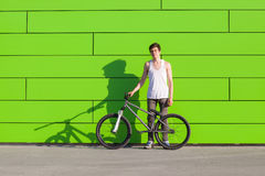 Boy with silver bike stay at green wall background Royalty Free Stock Image