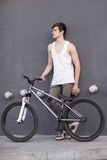 Boy with silver bike stay at grey wall background Stock Photos