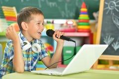 Boy singing karaoke. Portrait of boy singing karaoke with microphone and laptop stock image