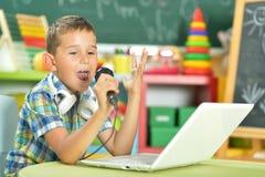 Boy singing karaoke. Portrait of boy singing karaoke with microphone and laptop stock photo