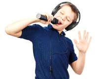 Boy singing into a microphone. Very emotional. Teenage boy in headphones, singing into a microphone on a white background. Very emotional stock photos