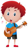 Boy singing while playing guitar Stock Photo