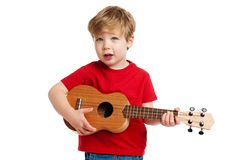 Cute Boy Playing Ukulele Guitar. Boy singing and playing guitar shot in the studio on a white background Royalty Free Stock Photography