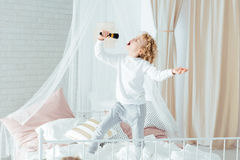 Boy singing, standing on bed Royalty Free Stock Images