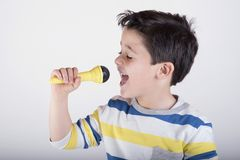 Boy singing to microphone Stock Images