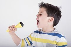 Boy singing to microphone. On white background Stock Photo