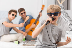 Boy singing to microphone. Happy boy wearing sunglasses singing to microphone royalty free stock photography