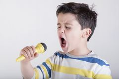 Boy singing to microphone. On white background Stock Image