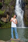 Boy singing at waterfall Royalty Free Stock Image
