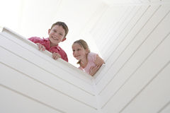 Boy With Sister Looking Over White Wall Royalty Free Stock Photos