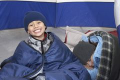 Boy With Sister Relaxing In Tent Royalty Free Stock Image