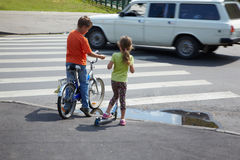 Boy and sister stand before zebra crossing stock images